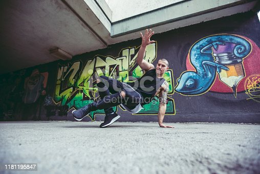 Young Caucasian handsome man performing breakdance tricks.