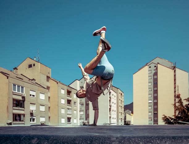 Breakdancer bailando sobre un techo en una ciudad - foto de stock
