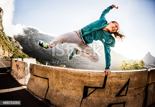 A breakdancing teen jumping over a wall parkour style