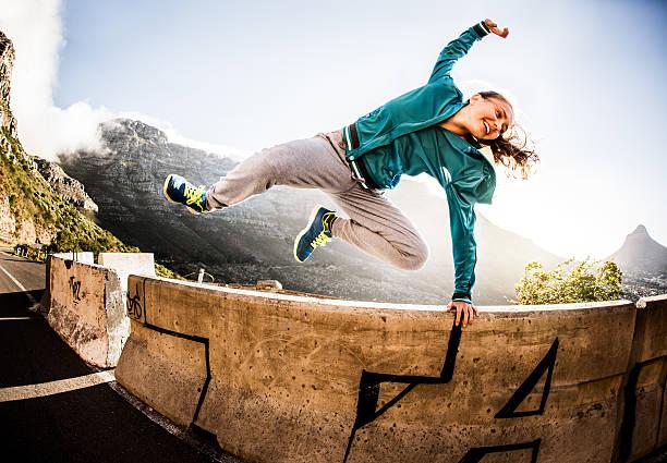 breakdancer voller vitalität springt über die mauer parkour- stil - parkour stock-fotos und bilder