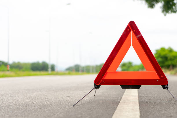 breakdown triangle stands alongside the road. Car broke down sign on road concept. breakdown triangle stands alongside the road. Car broke down sign on road concept. traffic accident stock pictures, royalty-free photos & images