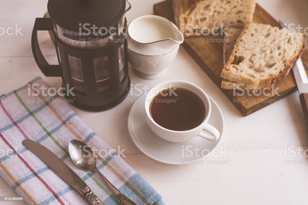 Breakfast - a cup of coffee, french press and fresh bread