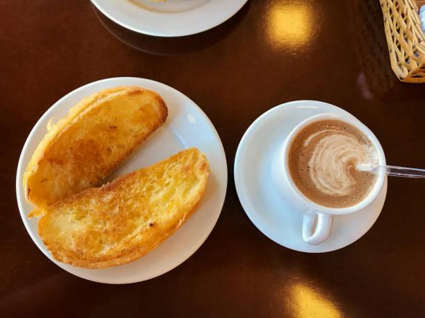 frühstück in brasilien mit baguette mit butter auf dem teller mit capuccino auf tisch geröstetes. - brot ohne weizen stock-fotos und bilder