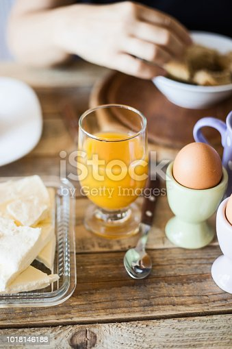 Breakfast - boiled eggs with fruit juice and cow cheese at dining table, close-up, selective focus