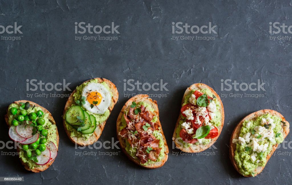 Breakfast avocado sandwich - with crispy bacon, quail egg, tomatoes, goat cheese, green peas, radish, cucumber. Healthy snack. On a dark background, top view, copy space stock photo