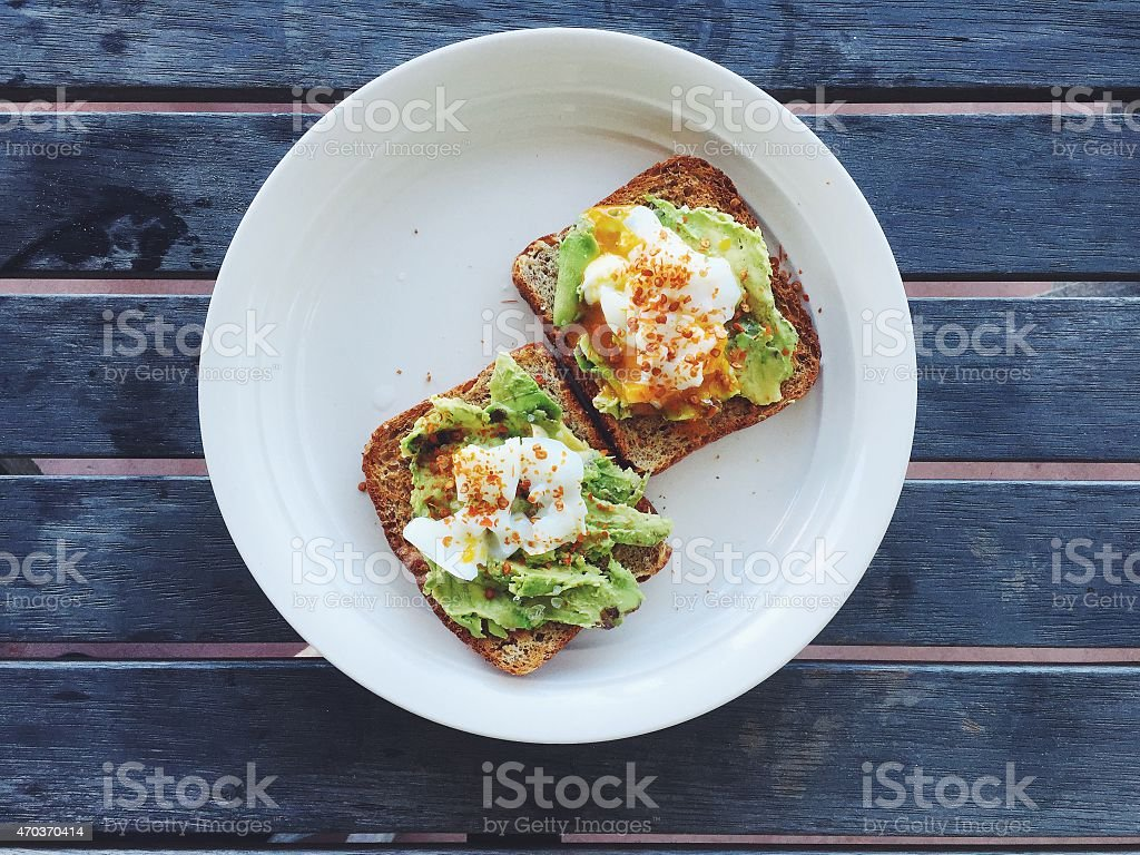 Breakfast: avocado toast with poached egg and chili flakes stock photo
