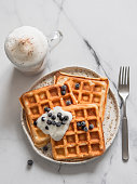 Delicious homemade baked belgian waffles with greek yogurt, blueberries and cappuccino on white marble background. Perfect breakfast with copy space for text or design. Top view or flat lay. Vertical