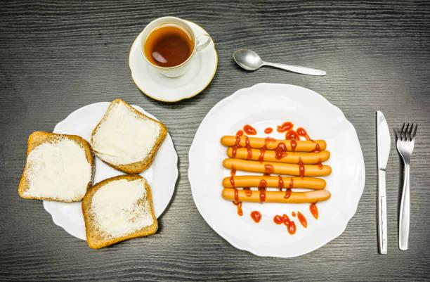 Kahvaltı sosis ketçap ile haşlanmış - tereyağı ve bir fincan çay ile dilim. Yukarıdan görüntüleyin. stok fotoğrafı