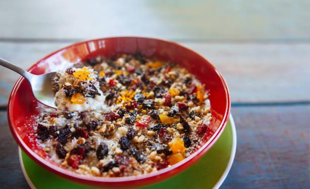 frühstück schüssel: müsli mit banane, kiwi, mango, rosinen und chia samen - haferflocken rosinen stock-fotos und bilder