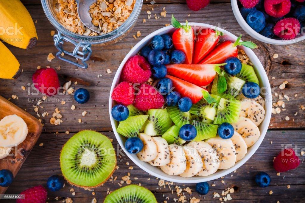 Breakfast bowl: granola with banana, kiwi, raspberry, strawberry, blueberry and chia seeds stock photo