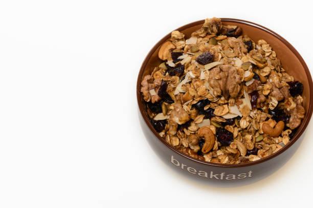 frühstück: schüssel vollkorn-müsli isoliert auf weißem hintergrund - haferflocken rosinen stock-fotos und bilder