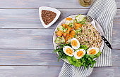 Breakfast bowl with oatmeal, zucchini, lettuce, carrot and boiled egg. Fresh salad. Healthy food. Vegetarian buddha bowl. Top view
