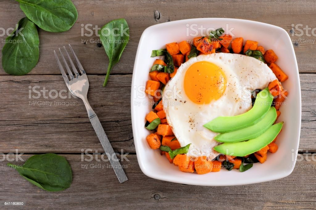 Breakfast bowl with sweet potato, egg, avocado and spinach over rustic wood stock photo