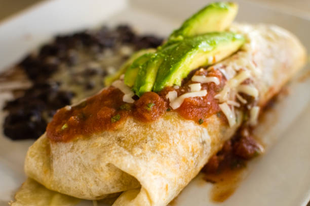 Breakfast Burrito with avocado and black beans on plate stock photo