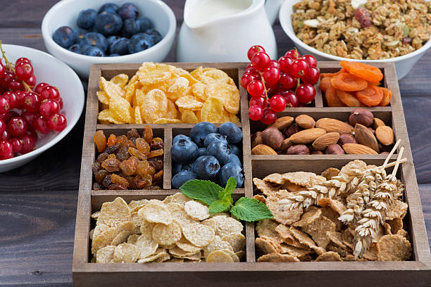 cereales de desayuno y otros ingredientes en una caja de madera - fibra dietética fotografías e imágenes de stock