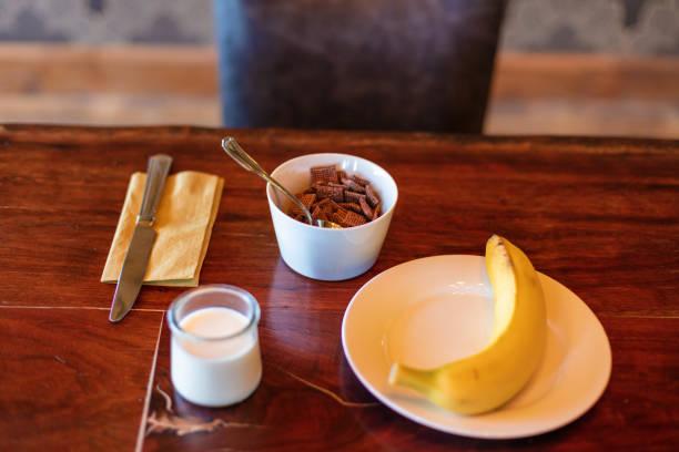 sarapan sereal warna-warni tempat pengaturan termasuk buah dan minuman - steamed banana potret stok, foto, & gambar bebas royalti