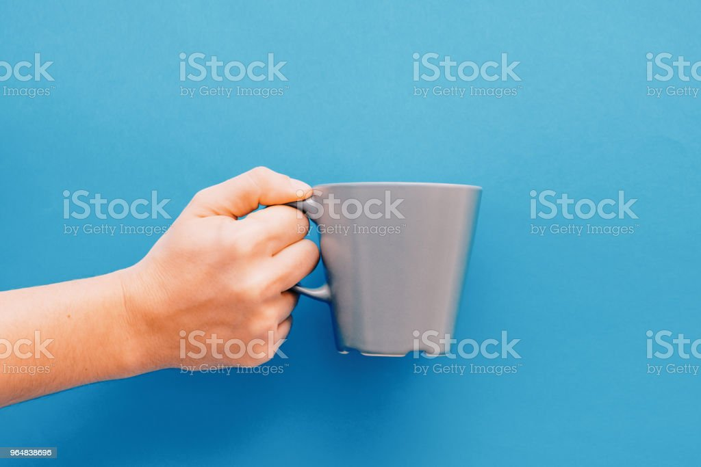 Breakfast concept.Hand holding mug isolated on blue background royalty-free stock photo