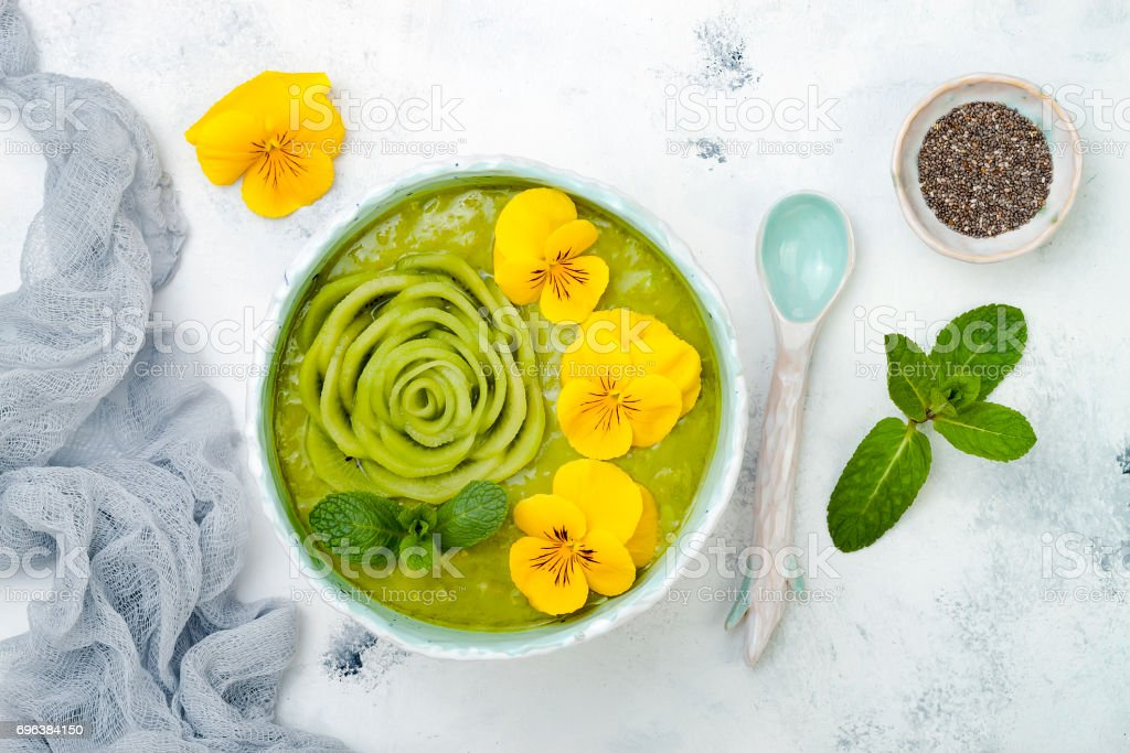 Breakfast detox green smoothie bowl topped with kiwi rose and edible Pansy flowers. Overhead, top view, flat lay stock photo