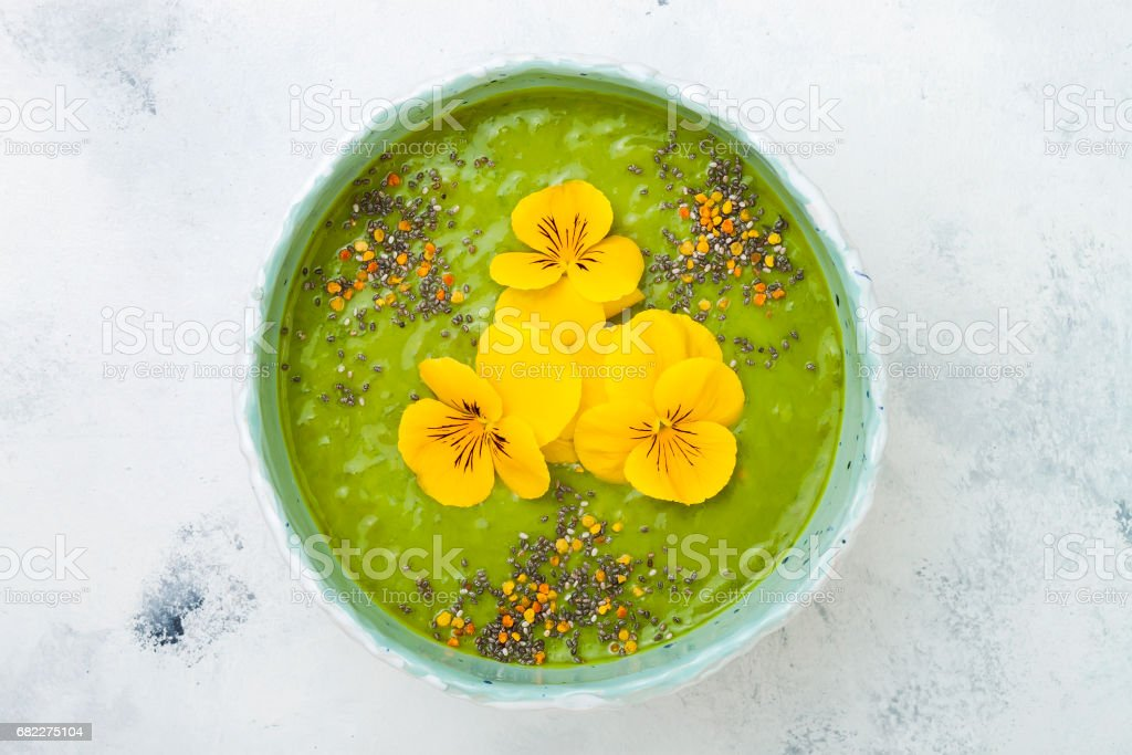 Breakfast detox green smoothie bowl topped with superfoods, chia seeds, bee pollen and edible flowers. Overhead, top view, flat lay, copy space stock photo