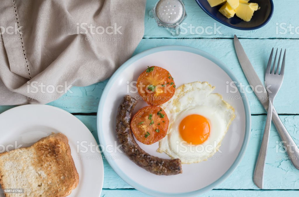 Breakfast dish with fried egg, sausage, tomato and toast. Overhead view stock photo