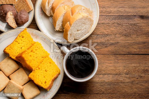 istock Breakfast food on a wooden table, carrot cake, bread, cookies and a hot coffee with steam coming out 1036340914