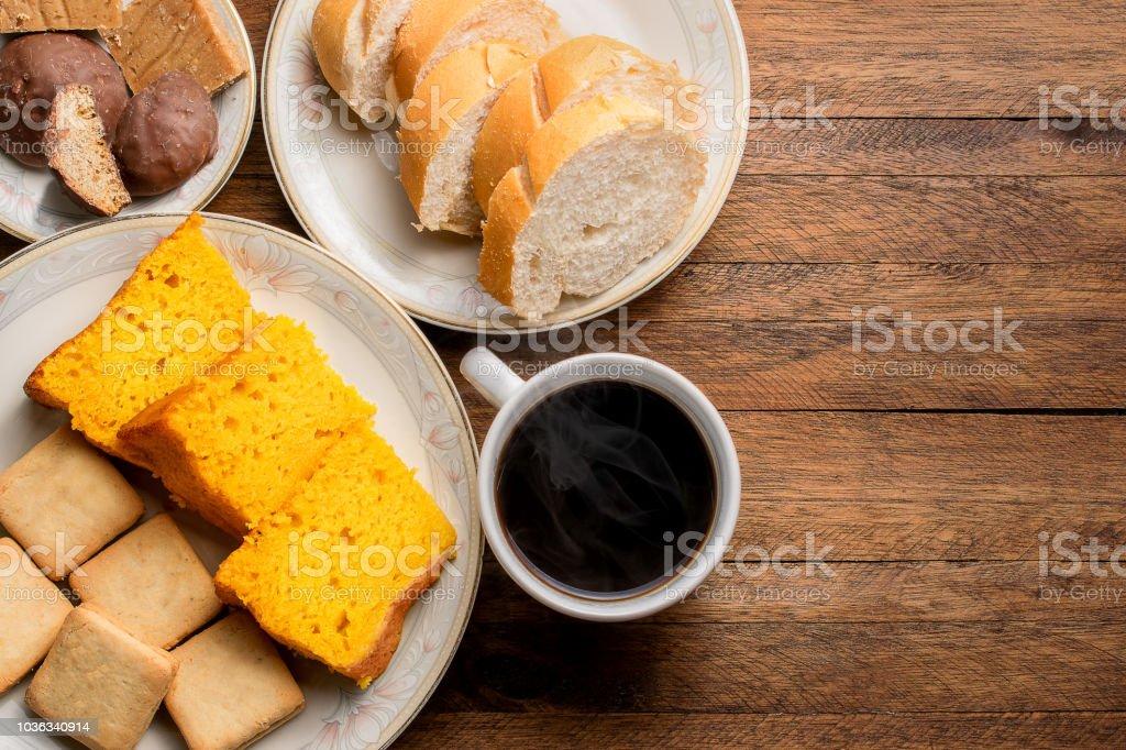 Café da manhã em uma mesa de madeira, bolo de cenoura, pão, biscoitos e um café quente com vapor saindo - foto de acervo
