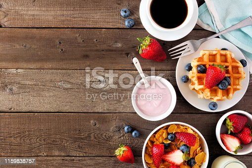 599887760 istock photo Breakfast food side border. Fruits, cereal, waffles, yogurt and coffee. Top view over wood with copy space. 1159838757