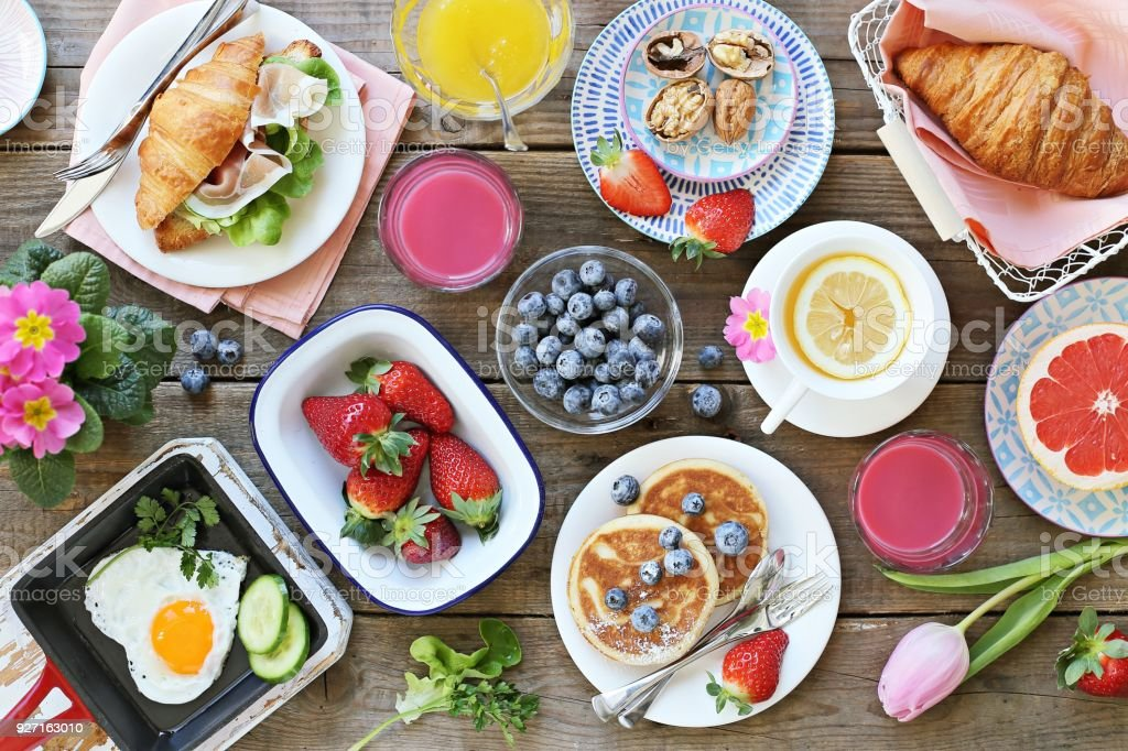 Breakfast food table. Festive brunch set, meal variety with fried egg, pancakes, croissants, smoothie ,fresh berries and fruits stock photo