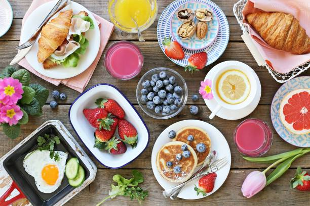 breakfast food table. festive brunch set, meal variety with fried egg, pancakes, croissants, smoothie ,fresh berries and fruits - поздний завтрак стоковые фото и изображения