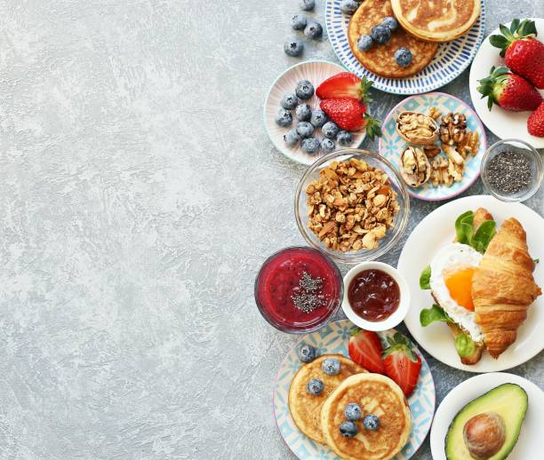 breakfast food table. festive brunch set, meal variety with granola, fried egg, pancakes, croissants, smoothie ,fresh vegetables, berries and fruits. - поздний завтрак стоковые фото и изображения