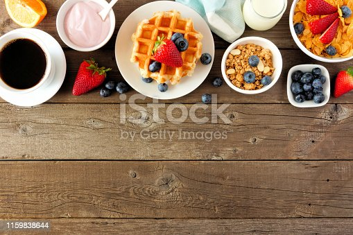 599887760 istock photo Breakfast food top border. Fruits, cereal, waffles, yogurt and coffee. Top view over wood with copy space. 1159838644