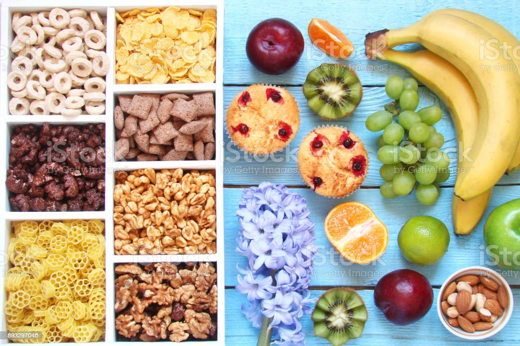 Breakfast for children, multigrain flakes, puffs, rings, popcorn in a wooden box and muffins with fruits on a blue background stock photo