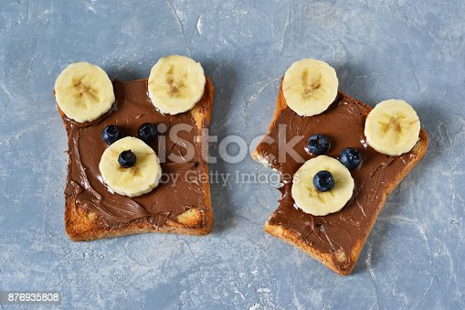 istock Breakfast for children - toast with chocolate paste, banana and berries. Good morning! 876935808