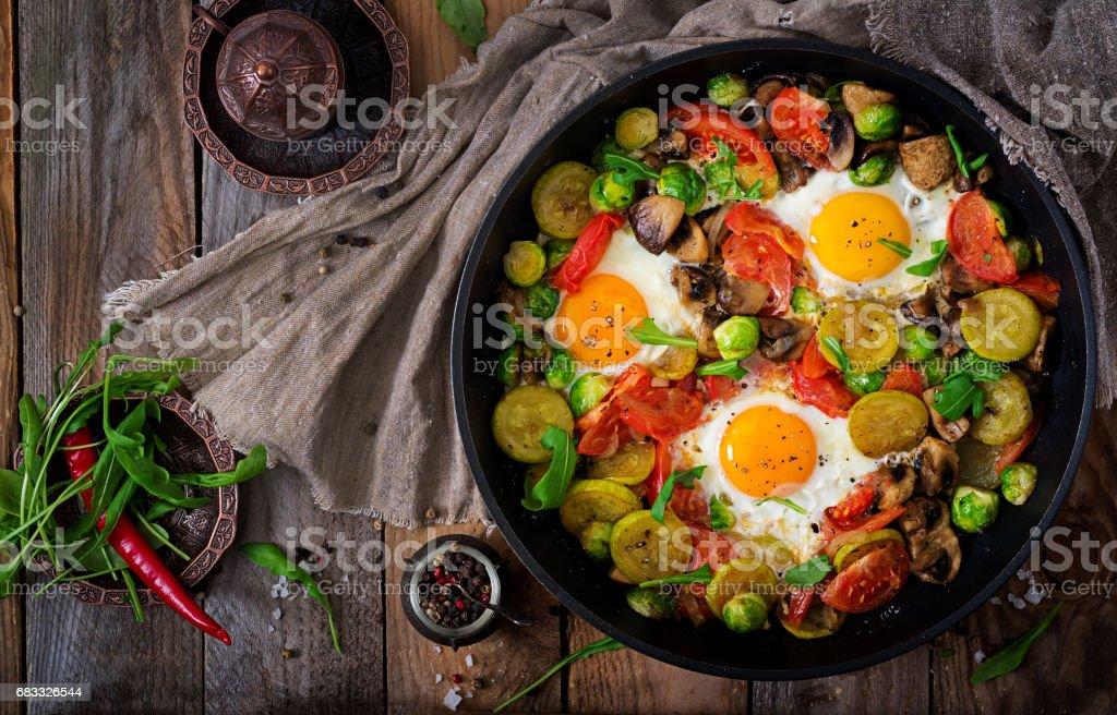 Le petit déjeuner pour deux. Œufs frits aux légumes - shakshuka dans une poêle sur un fond en bois dans un style rustique. Poser de plat. Vue de dessus photo libre de droits