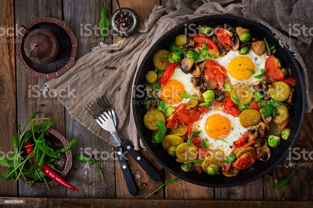 Breakfast for two. Fried eggs with vegetables - shakshuka in a frying pan on a wooden background in rustic style. Flat lay. Top view royalty-free stock photo