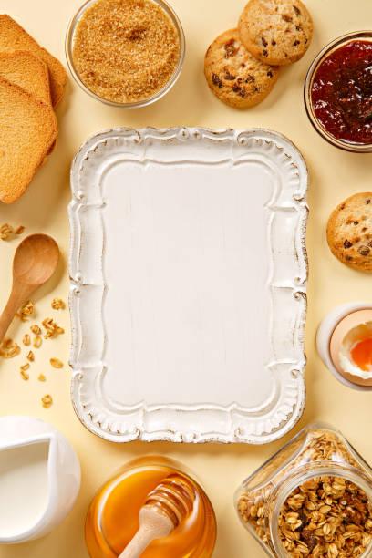 frühstück-frame von oben gesehen. frisches und gesundes frühstückszutaten (marmelade, toast, zucker, cookies, eiern, honig, milch, müsli). kopieren sie raum. ansicht von oben - tablett holz stock-fotos und bilder