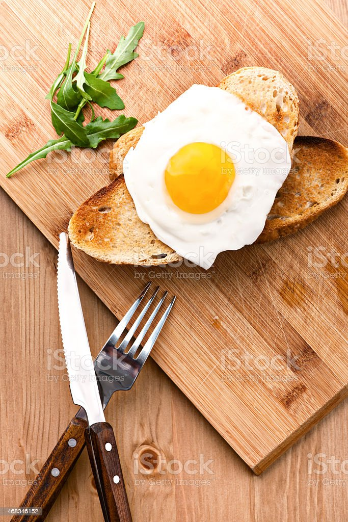 Breakfast fried egg fork knife on the table with toast royalty-free stock photo