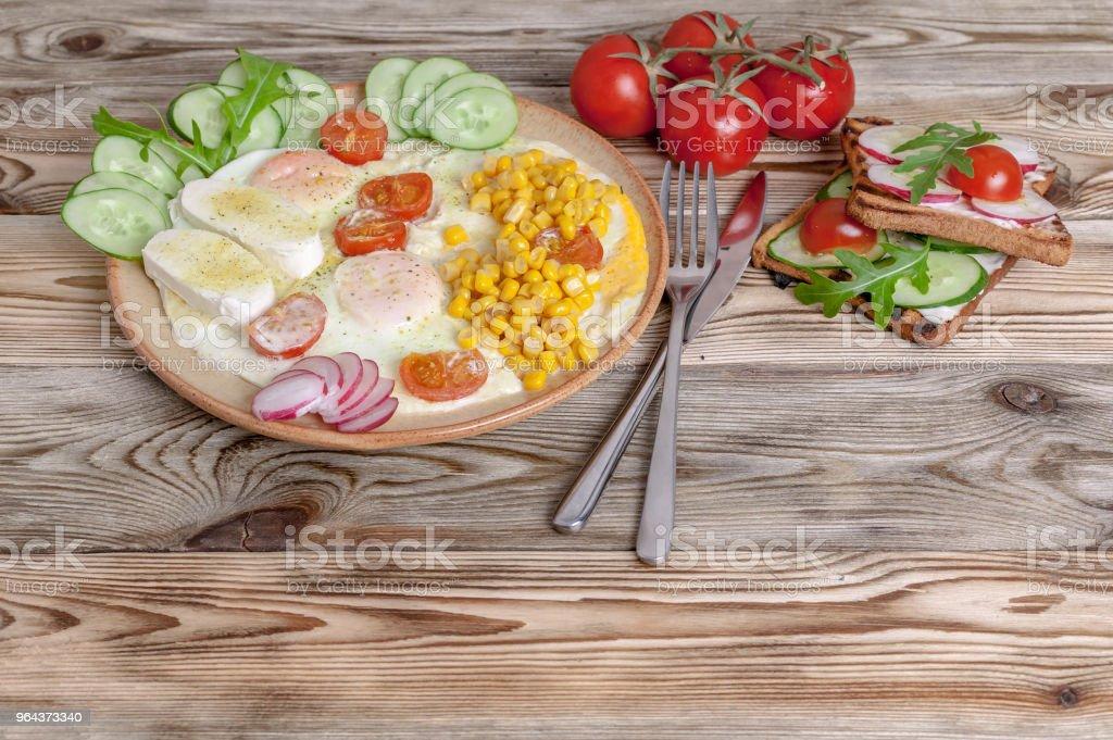 Pequeno-almoço. Ovos fritos com tomate cereja, queijo mussarela, legumes frescos e sanduíches caseiros. Conceito de pequeno-almoço saudável. - Foto de stock de Almoço royalty-free