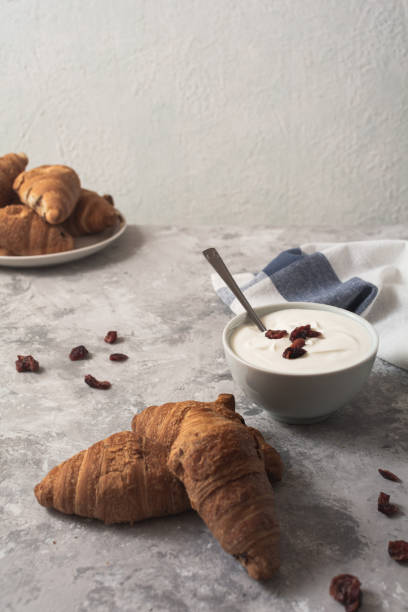 Breakfast: Homemade croissants and yoghurt with sweet dried rose hips stock photo