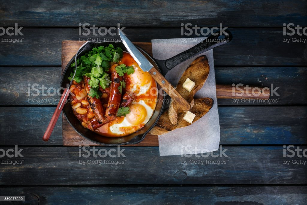 Breakfast in a hot frying pan with fried eggs, sausages, beans, greenery and toasts. On a colored wooden background with cutlery. Top view stock photo