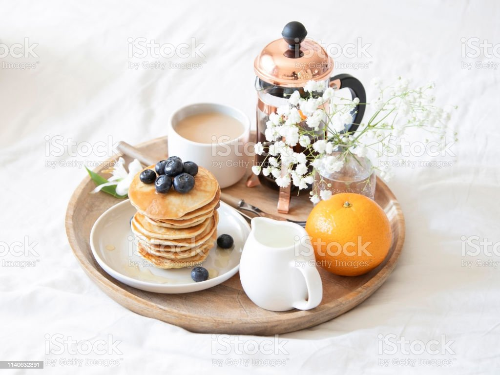Breakfast in bed. Pancakes with blueberries and honey, coffee, milk...