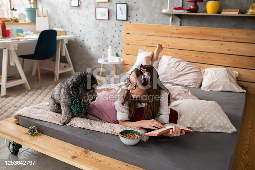 Young woman reading and trying to eat breakfast ,her dog looking at the bowl being hungry