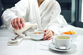 Woman pouring milk in a bowl for a breakfast in a hotel room.