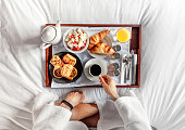 A Man Having Breakfast on a bed in a Hotel Room. Flat lay