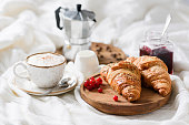 istock Breakfast in bed with croissants, coffee and jam 897027610