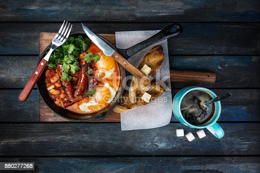 istock Breakfast in on a hot frying pan with fried eggs, sausages, beans, greenery and toasts. With coffee rafinated sugar and cutlery. Top view 880277268