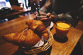 Table with breakfast - caffe, hot chocolate and croissant