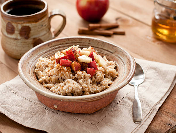 Breakfast made of oatmeal with apples, honey and cinnamon  Rustic pottery bowl of steel cut oatmeal with apples, honey, and cinnamon and a cup of coffee. oatmeal stock pictures, royalty-free photos & images