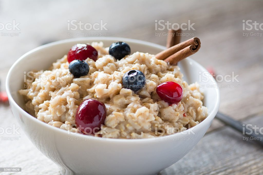 Breakfast oatmeal porridge with berries in bowl stock photo