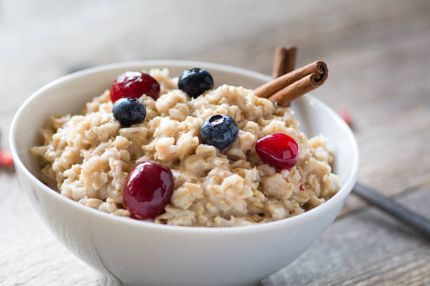 Breakfast oatmeal porridge with berries in bowl Oatmeal porridge with cinnamon, blueberries and cranberries in white bowl, close up selective focus image oatmeal stock pictures, royalty-free photos & images